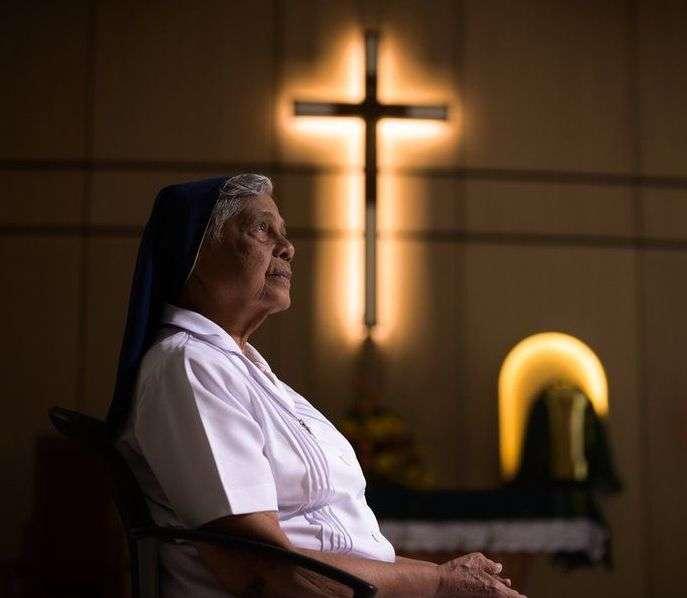 Nun sitting in chair beneath cross