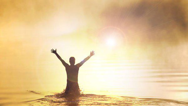 Man standing in sea with arms outstretched towards sun