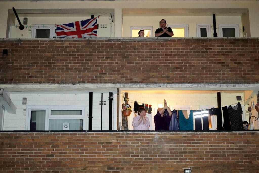 People on balcony clapping NHS