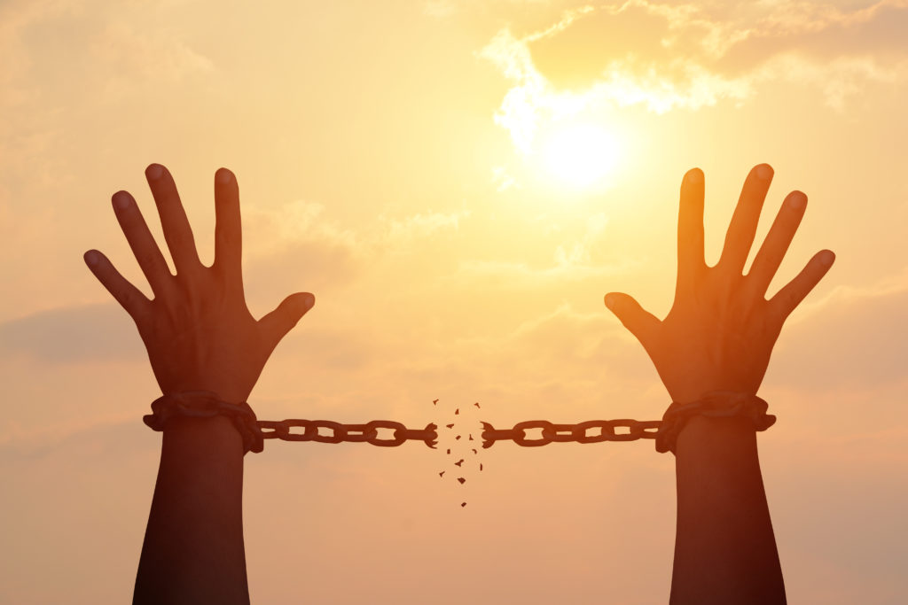 Hands raised with chains broken